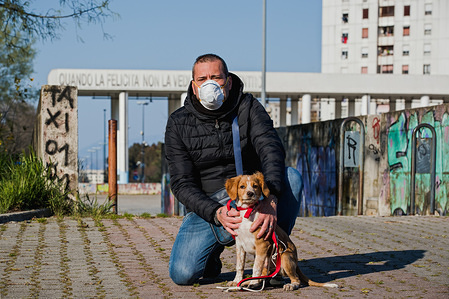A man wearing a face mask as a preventive measure, posing with his dog during quarantine. Following the covid19 pandemic that has hit Italy strongly, the Prime Minister, Giuseppe Conte has ordered strong restrictions for the quarantine to minimize the spread of the corona virus.