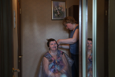 Oksana, professional hair stylist gives a haircut to Liudmila her mother-in-law at her house as all barbershops were ordered to close in an attempt to prevent the spread of coronavirus (COVID-19)