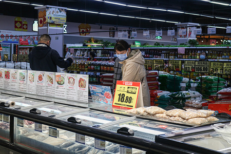 A woman wearing a sanitary mask as a precaution against the spread of coronavirus buys frozen meat in a supermarket.