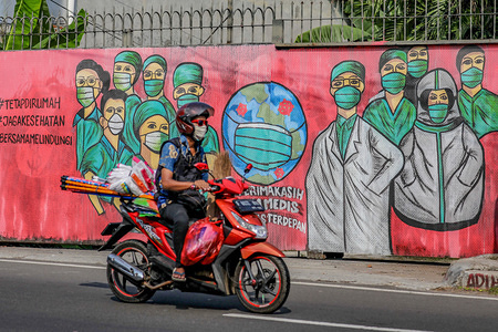 A motorist rides past a mural appreciating doctors and medical personnel for fighting COVID-19, in Jakarta.