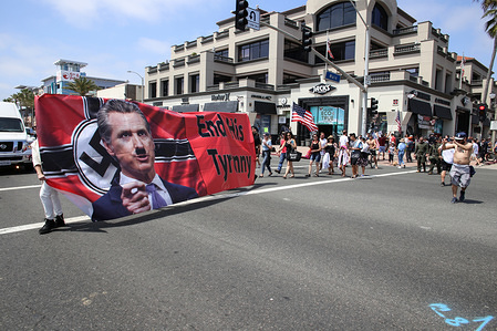 Protesters hold a banner that says End His Tyranny with a photo of California Governor Gavin Newsom portrayed as a Nazi during the demonstration. Citizens staged a protest in front of the Huntington Beach Pier to demand for the reopening of the California economy.