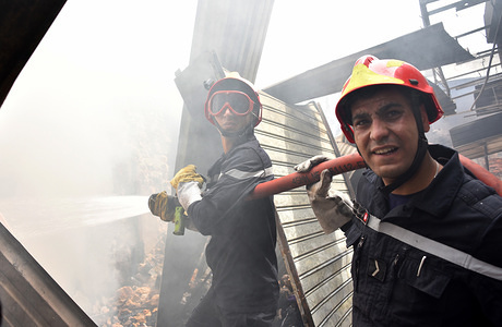 TUNIS, TUNISIA - MAY 13, 2020: Civil protection workers trying hard to extinguish the fire. The cause of a fire in Hafsia thrift stores that nearly damaged 30 stores, remains unknown at this time.