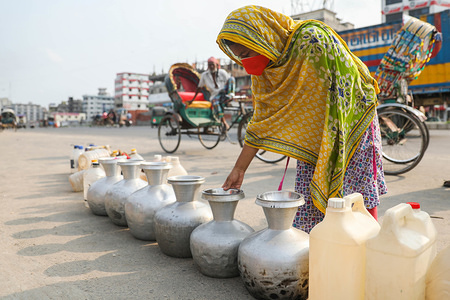A woman line up pitchers and jerrycans to collect water amid the water crisis on the scorching summer day during Coronavirus (COVID-19) crisis. There is a water shortage in Dhaka and people all over town are in search of where to find water.