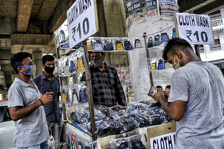 People wearing face masks as a preventive measure buy face mask at a street stall during the Lockdown. At the beginning of the fourth phase of a nationwide lockdown in Kerala, several relaxations and new guidelines for the state are to be followed during this period of the prolonged lockdown.