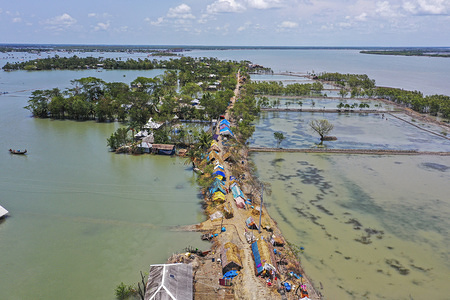 (EDITORS NOTE: image taken with a drone) In coastal area's people take temporary shelter on the embankment after the landfall of cyclone Amphan last month at Koyra in Khulna. Thousands of shrimp enclosures have been washed away, while numerous thatched house, trees, electricity and telephone poles, dykes and croplands were damaged and many villages were submerged by the tidal surge of the Amphan in Khulna District.