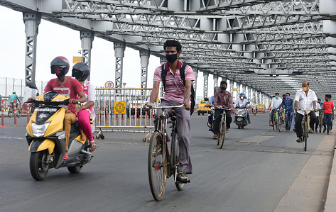 A man is seen wearing a face shield as he rides his bicycle to work following the relaxation in the 5th phase of lockdown. Despite the increasing Covid-19 positive cases, the government of India along with state governments have  given relaxation in the 5th phase of lockdown. With the opening of offices and markets, employees have to work but due to restriction and scarcity in public transport along with huge taxi fares many have resorted to using bicycles to get to their work places.