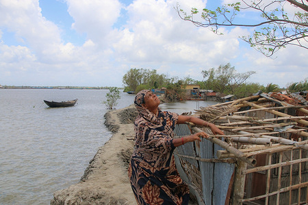 A helpless woman puzzled after losing her house after the landfall of cyclone Amphan. Thousands of shrimp enclosures have been washed away, while numerous thatched house, trees, electricity and telephone poles, dykes and croplands were damaged and many villages were submerged by the tidal surge of the Amphan.