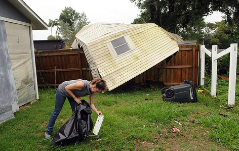 Elizabeth Ellis picks up debris after her shed and fence were destroyed, during the aftermath of Tropical Storm Cristobal. A tornado spawned by Tropical Storm Cristobal passed through Orlando, Florida leaving at least 8 homes damaged by the EF1 tornado, along with numerous reports of downed trees and power lines. No injuries have been reported.