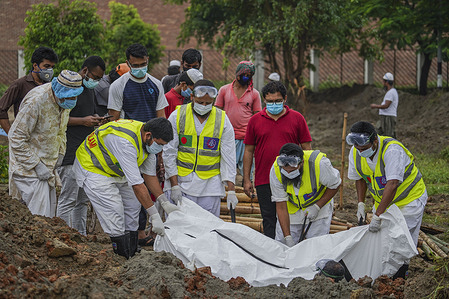 (EDITOR'S NOTE: Image depicts death) Volunteers carry the body of a deceased Coronavirus (COVID-19) victim during a funeral while dressed in protective suits and face masks as a preventive measure. Government sought the assistance of volunteers from different organisations as the fatality rate grew with the spread of novel coronavirus across the world, the burial of Covid-19 victims, following the World Health Organisation guidelines – including maintaining social distancing.