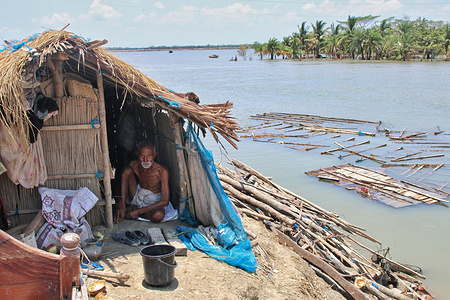 A man sits under a temporary shelter on the embankment during the aftermath of the cyclone amphan. Thousands of shrimp enclosures have been washed away, while numerous thatched houses, trees, electricity and telephone poles, dykes and croplands were damaged and many villages were submerged by the tidal surge of the extremely severe cyclonic storm amphan in Khulna division.