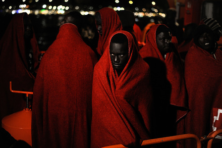 Migrants seen covered with red blankets to keep them warm during the disembarking. Arrival of a group of migrants rescued in the Mediterranean Sea from a dinghy. Aboard of a boat, members of the Spanish Maritime Safety rescued a total of 48 migrants (of them, some minors and womens) near the Malaga coast and brought them at the Port of Malaga, where they were assisted by the Spanish Red Cross.