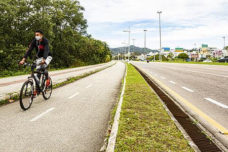 A man wearing a face mask as a preventive measure rides a bicycle along the bike lane at Professor Henrique da Silva Fontes Avenue.