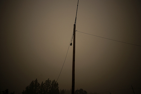 A light pole is surrounded by smoke from the wildfires. Wild Fires in Colton, Oregon rage on as firefighters attempt to quell the fires and locals attempt to decipher whether or not the fires were started naturally or by arsonists.