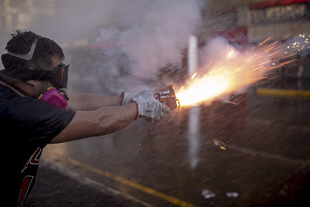 """A protester launches fireworks during the protest in Santiago. Hundreds of protesters confront the police in the vicinity of the Plaza Baquedano, renamed """"Plaza de la Dignidad"""" by the people to demand justice for Antoni, a 16-year-old who was thrown from a bridge by police during the previous protest day."""