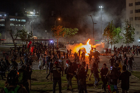 """An Armoured vehicle of the Chilean Carabinieri special forces is attacked with Molotov cocktails during the demonstration. Hundreds of people gathered at the Baquedano square renamed by the protesters as """"Plaza de la Dignidad"""" to protest against the administration of President Sebastian Piñera and the police brutality."""