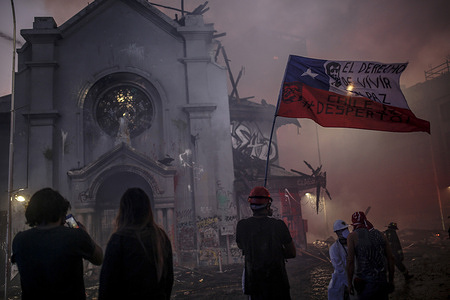 People stand outside the burning Church of Asuncion after it was set on fire during the demonstration. Hundreds of thousands of people demonstrated in Plaza Baquedano to commemorate October 18, 2019, where the large protests began against the government of Sebastián Piñera in Chile, who responded with a state of emergency, a curfew and soldiers in the streets.