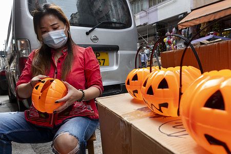 A gift and decorative product store vendor put together Halloween pumpkin theme baskets to sell on Halloween day.