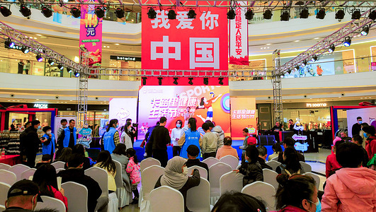 """People watch a performance on a stage with a huge banner with a slogan """"China I love you"""" in the background in Yinchuan."""