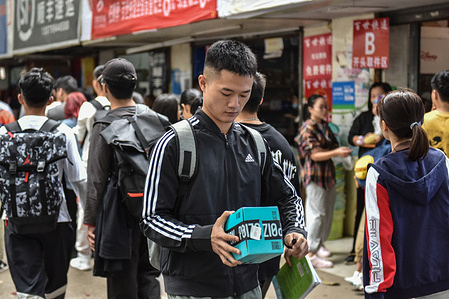 A college student carrying a package which he just picked up from from a online shopping pick up point during China's online shopping festival where businesses attract a lot of consumers through discounts and promotions.