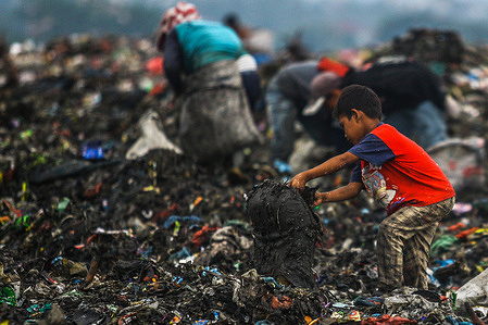A child of a scavenger community, helps his parents who work as scavengers sort through a pile of garbage for recycling.