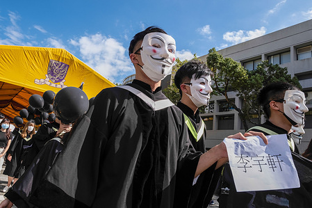 Graduating students wearing Guy Fawkes masks hold placards with the names of the twelve protesters detained on the mainland during a protest march at the Chinese University of Hong Kong (CUHK).In a pro-democracy protest at the Chinese University of Hong Kong (CUHK), graduating students wearing gowns and masks displayed and chanted slogans that the government had declared illegal according to the new national security law.