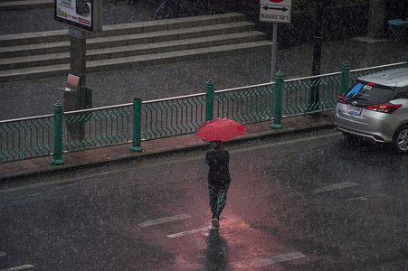 A person walks across Ratchadamri Road while holding an umbrella on a rainy day.