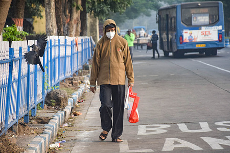 A man walks along the road while wearing winter clothes.Kolkata people got to feel the winter chill which is three degree below the normal temperature. Though the temperature will have been steadily dropping as a depression has formed over the Bay of Bengal near the Tamil Nadu Puducherry coast.