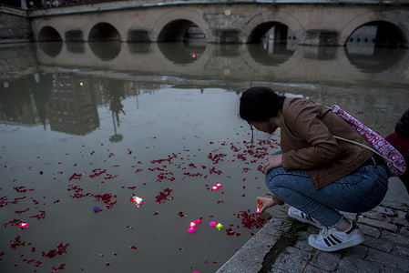 """A girl puts a candle into the Genil River river during the International Roma Day. People from Granada (Spain) take part in  the """"River Ceremony"""" on April 6th, an act of the International Roma Day, celebrated each April 8th around the world since 1990. It commemorates the first World Romani Congress, celebrated in Chelsfield near London  in 1971"""