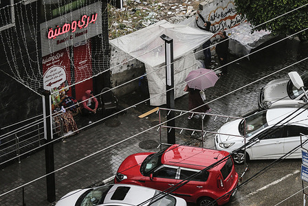 A Palestinian walking under an umbrella down the streets during a rainy day.
