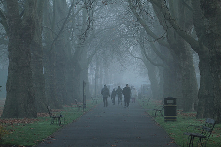 People walk through the morning fog in Plashet Park, Newham. Most parts of London were engulfed in fog.