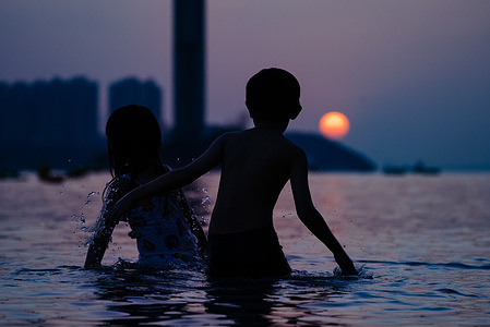 Two kids are seen playing in beach waters during the sunset.