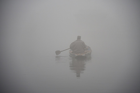 A man rows his boat on Dal lake during a dense fog in Srinagar. Night temperatures across Kashmir dropped below the freezing point. Morning chill and dense fog kept most Kashmiris indoors till a feeble sun started struggling its way through a thin layer of winter clouds.