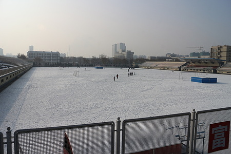 Students are seen crossing a stadium covered by snow at Ningxia university.