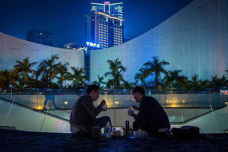 Two men having dinner take-away in Tsim Sha Tsui, Hong Kong as citizens are not allowed to dine-in at restaurants after 6 pm.