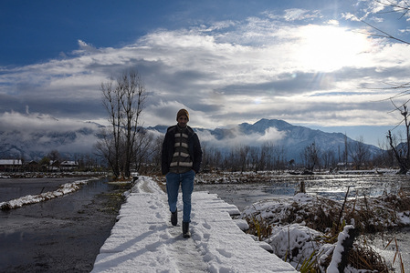A man walks on snow covered wooden bridge after a first spell of Snowfall in Srinagar. The season's first snowfall lashed the plains of the Kashmir Valley while the higher reaches of Jammu and Kashmir received heavy snowfall. All major highways including the Srinagar-Jammu, Srinagar-Leh and the Mughal Road are closed for traffic following heavy snowfall, officials said.