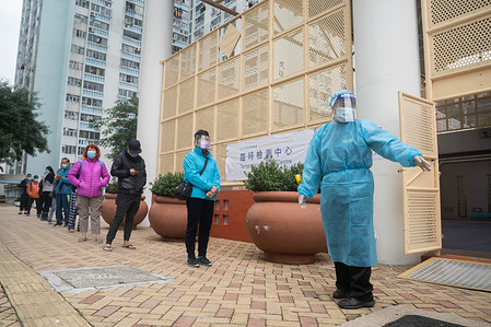 A health worker seen dressed up in her PPE (Personal Protective Equipment) as residents from a public housing estate line up to have their Covid-19 swab test done at a makeshift Covid-19 testing centre. Multiple makeshift Covid-19 coronavirus testing centres are set up in Hong Kong to provide free of charge testing services for residents.
