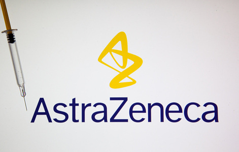 In this photo illustration, a medical syringe seen displayed in front of the AstraZeneca's logo. AstraZeneca is an English drug company.