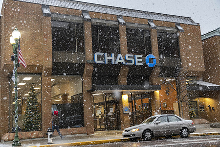 A man walks in front of a Chase bank on Court Street. Athens, Ohio gets a bit of snow in the downtown area.