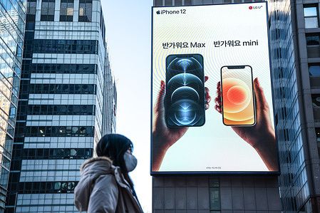 A woman wearing a protective mask walks past an iPhone 12 advertisement in Seoul.