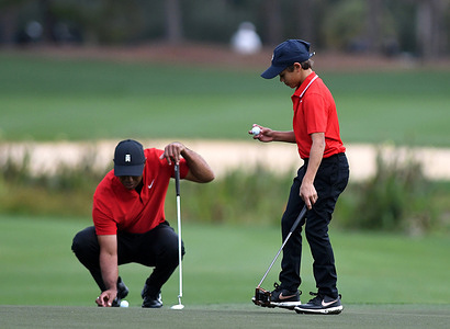 Tiger Woods and his son Charlie prepare to putt on the second hole during the final round at the PNC Championship golf tournament at the Ritz-Carlton Golf Club.