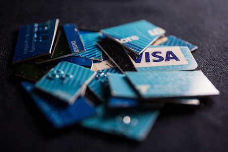 In this photo illustration, Visa credit card cut into pieces seen displayed.