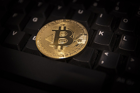 In this photo illustration, the Bitcoin golden cryptocurrency commemorative coin seen on a black keyboard.