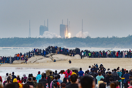 A crowd of people outside watching the launch of China's new medium-lift carrier rocket Long March 8, on its maiden flight, the rocket put five satellites into orbit.  The Long March 8, the latest in China's Long March launch vehicle fleet, lifted off at 12:37 pm on Tuesday from a coastal Launchpad at Wenchang Space Launch Center in southern China's Hainan province.