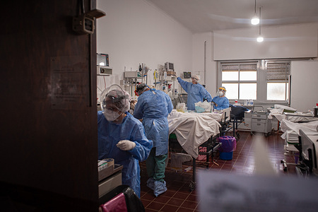 Healthcare workers dressed in protective suits treat infected patients inside the COVID-19 ICU at Hospital Gral. San Martín in Firmat, Argentina. The city with a population of roughly 25000 people, has had 27 dead to date, and over 1000 confirmed positives.