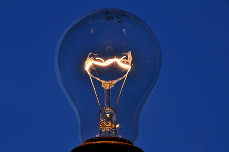 In this photo illustration an incandescent electric bulb lit against a background of the evening sky. An increase in electricity prices of at least 2% should be decided in January 2021, in France.