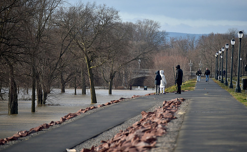 People are seen looking at the Susquehanna River as it rises and threatens to flood the area. The Susquehanna River is swollen outside of its banks due to rain and snowmelt. The river is projected to crest well above 20 feet on Saturday which is flood stage. Low lying areas not protected by the levee flood wall are expected to see flooding.