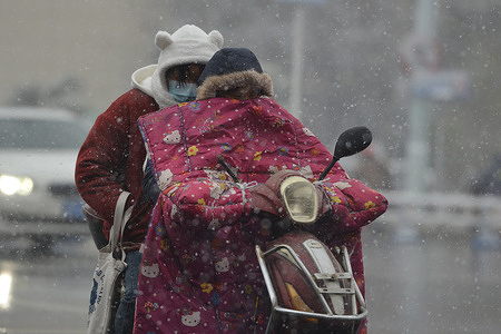 A resident wearing a winter jacket rides with a passenger in the snow in Fuyang. Temperatures drop to -8 C in the Fuyang. China's meteorological authority issued an alert for a cold wave as a strong cold front will sweep across most parts of Central and East China.