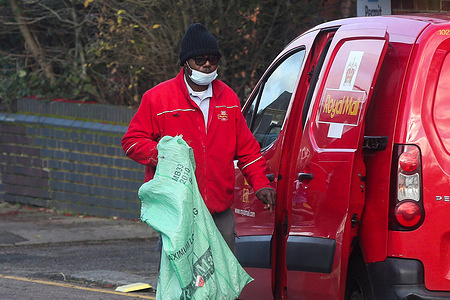 A postman wearing a face mask holds a postal sack in London.