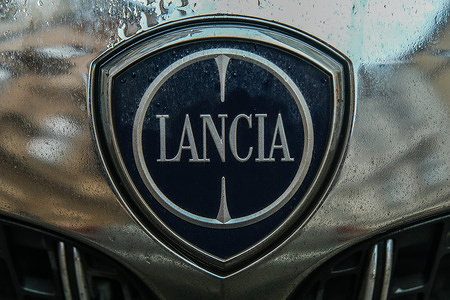 A Lancia logo seen displayed on a parked car.