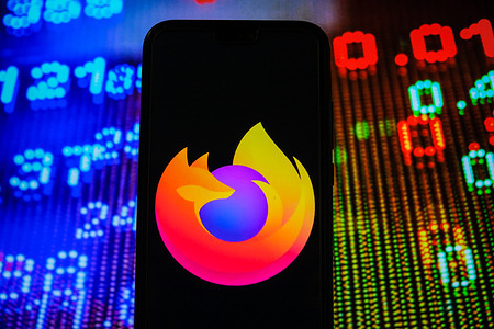 In this photo illustration, a Mozilla Firefox logo seen displayed on a smartphone with stock market prices in the background.
